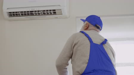 conditioner : Senior man in blue overalls repair air conditioning Stock Footage