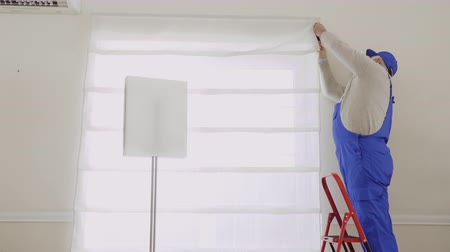 rolety : Mature master repair fastening of roller blinds