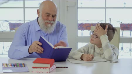 schoolkid : Grandpa with grandson makes school homework together Stock Footage