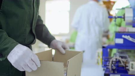 job transfer : Man packs product into cardboard box