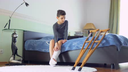 kule : Boy with broken leg sits on the bed Wideo