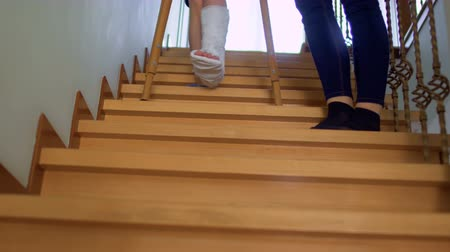 kule : Mother help her son with broken leg to move down the stairs