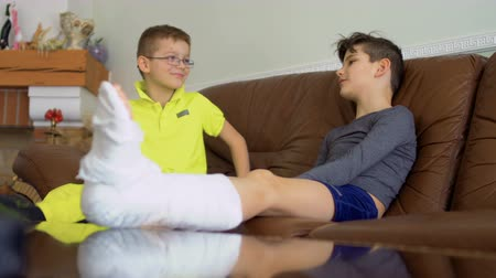 gips : Two brothers with broken leg and hand sitting on sofa at home and talking Wideo