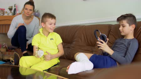 bandage : Two brothers with broken hand and leg are fooling at home sitting on sofa