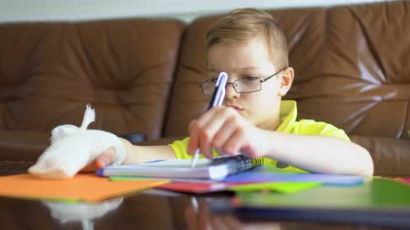 gips : Cute boy with broken hand makes his homework Wideo