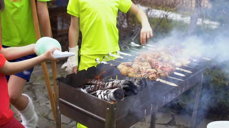 gips : Three boys grill meat at open air