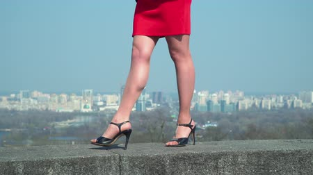 sexy heels : Female in red dress and in shoes on high heels walks at blurred city background