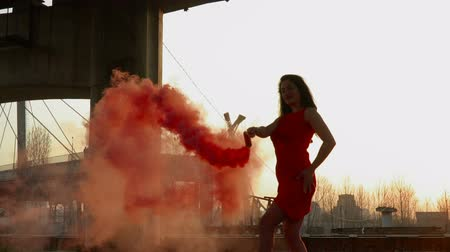 abandonment : Gorgeous woman with red smoke flare dancing under abandoned bridge