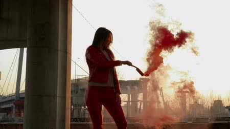 abandonment : Elegant girl in red costume dancing with red smoke near old constructions