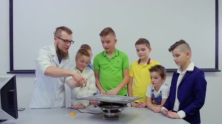 fraction : Lab assistant shows boys dancing sand on chladni plate Stock Footage