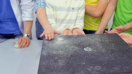 fraction : Children looks at Chladni plate with dancing sand Stock Footage