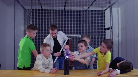 помощник : Group of boys explore Tesla coil in museum of popular science and technology Стоковые видеозаписи