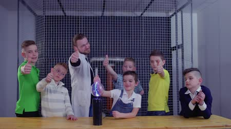 разряд : Children and teacher shows thumbs up holding glass globe over Tesla coil