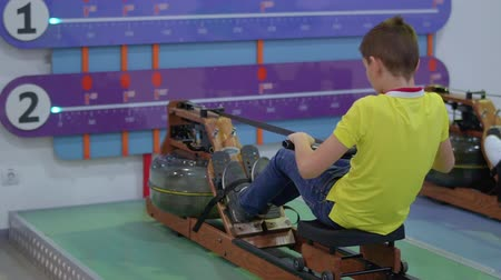тянуть : Boy makes sport exercises on training apparatus in scientific museum