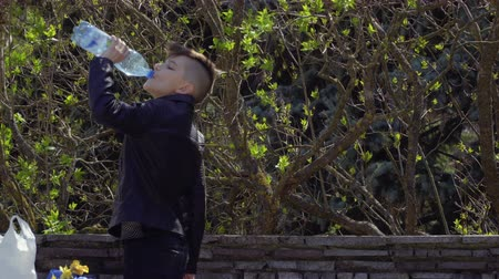 закалки : Teenager drinks water in park