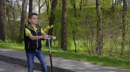 narcyz : Adorable boy with narcissus riding on kick scooter in park Wideo