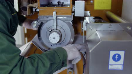 рукоятка : Worker adjust the paper tape inside the machine for making tea bags