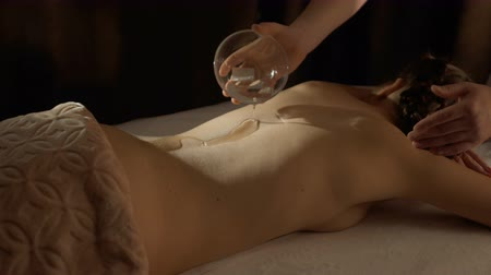 lényeg : Masseur pours olive oil on the back of client in spa center