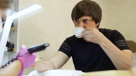 sanitize : Young man relax and drinking coffee during the procedure of manicure