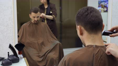 kuaför : Hairdresser cuts hair of man with electric razor Stok Video