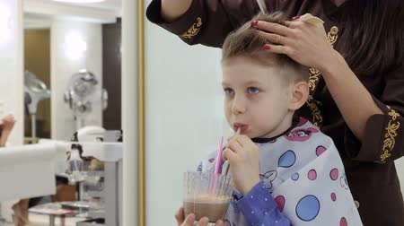modelo de moda : Cute boy drinks cocktail during hairdresser cuts his hair in barbershop Stock Footage