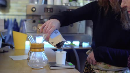 glass pitcher : Barista put coffee beans at scales and measure it for one portion of coffee