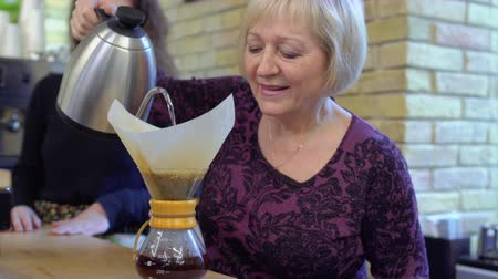 water show : Granny-barista pour hot water inside the jug with coffee