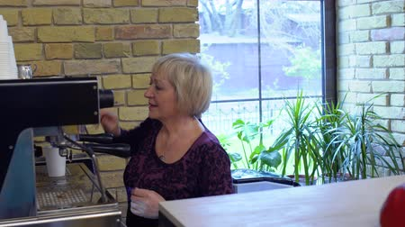 kafeterya : Mature woman make coffee for visitor in coffee shop