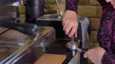 portafilter : Old barista tamp grinded coffee in portafilter