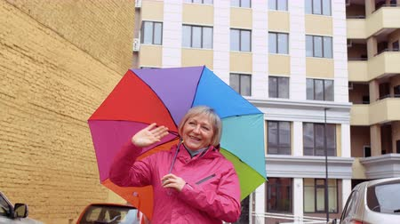 avlu : Senior woman with colorful umbrells meet someone at the street