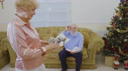 reminder : Senior woman look her old photos, her husband read book sitting at sofa