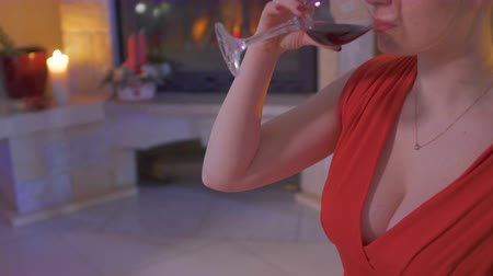 болваны : Young woman in red dress with big decollete drink red wine