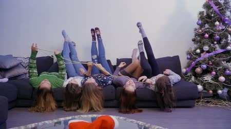 носок : Girls lying upside down on sofa and have fun