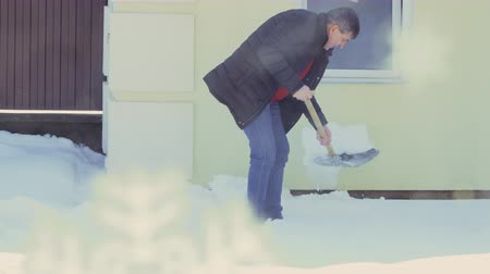fazla : Man with spade clean snow near house