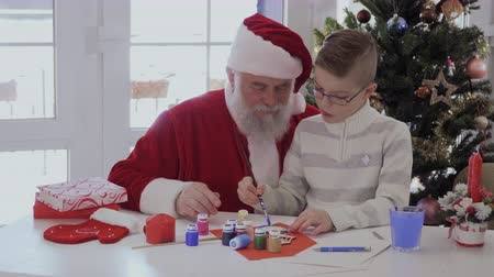 hand crafted : Santa Claus and little boy decorate hand-made article from wood with paints