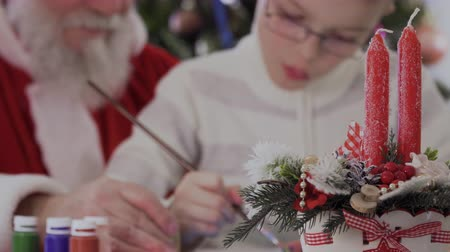falsificação : Santa and little boy draw picture at blurred background of two festive candles Stock Footage