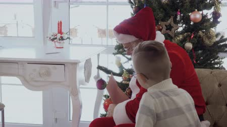 давать : Santa Claus give present to little boy after reading his wish list
