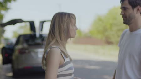 go away : Young man and woman quarreling at the road, man leaves his girlfriend Stock Footage