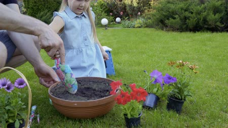clay pot : Father help little daughter to dig hole in the soil in the pot for flowers