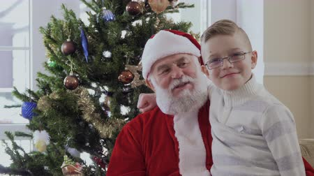 тянуть : Little boy hugging with Santa Claus