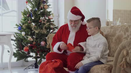 obálka : Little boy brings to Santa wish list and receive present Dostupné videozáznamy