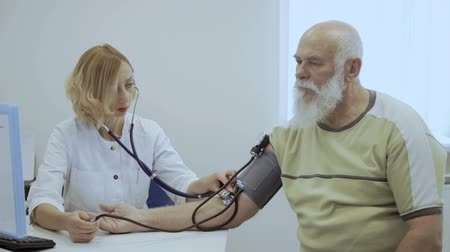 cardiologista : Doctor check pulse of old man with tonometer and stethoscope