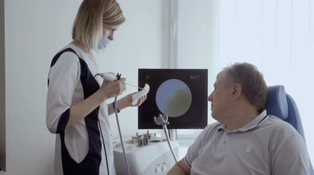 impaired : Doctor check nose of senior man with ENT telescope