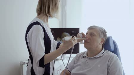 impaired : Doctor examine nose od adult man with ENT telescope Stock Footage