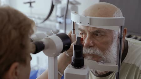 phoropter : Doctor check eyesight of senior man with biomicroscope Stock Footage