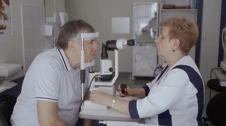 wzrok : Doctor examining eyesight of adult man with modern equipment