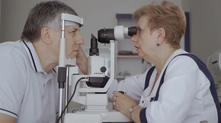 phoropter : Adult man check his eyesight with special optical equipment Stock Footage