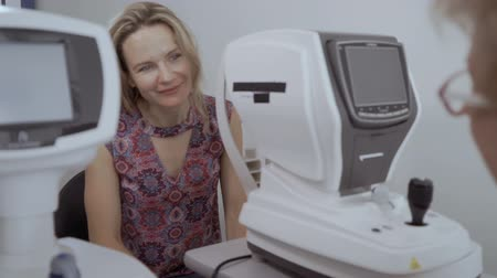 phoropter : Young woman listen oculist after checking her eyesight on modern equipment