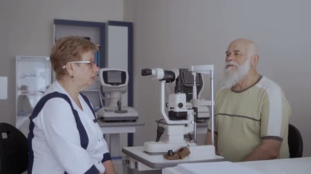 phoropter : Ophthalmologist talk with old patient after checking his vision