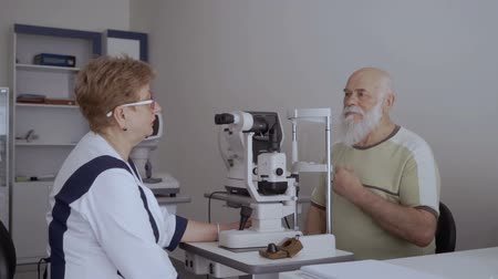 phoropter : Oculist give consultation to old man Stock Footage